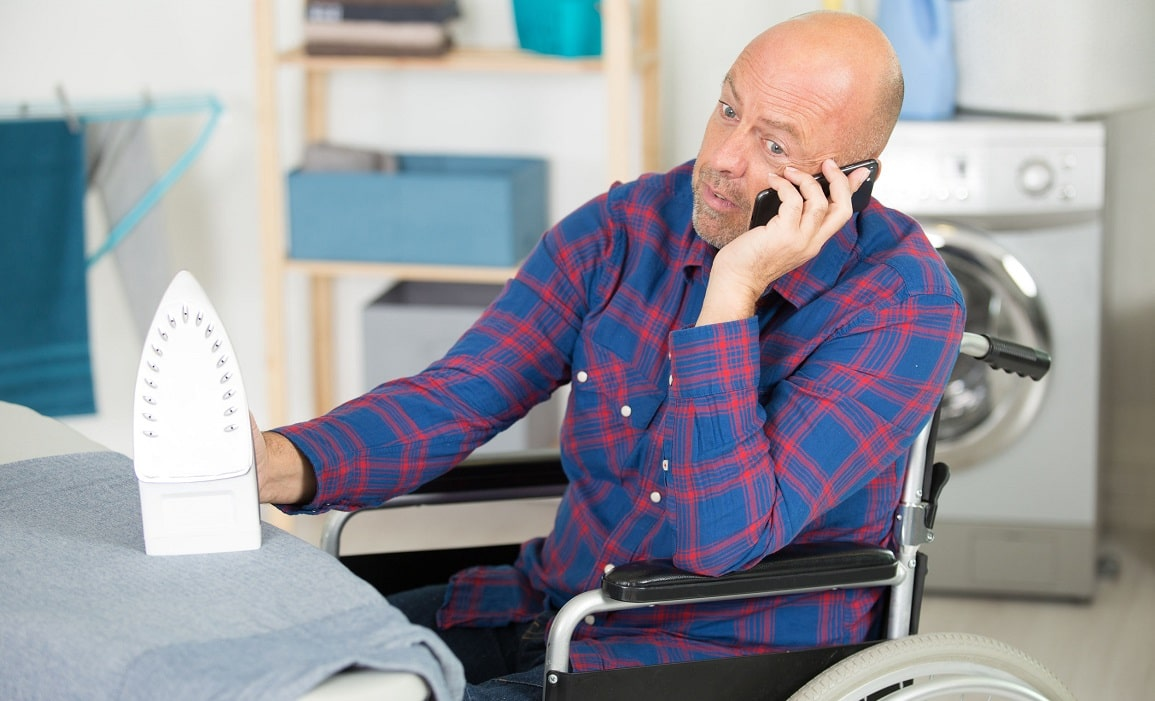 Daily Living Aids - Man in a wheelchair ironing whilst talking on his mobile phone