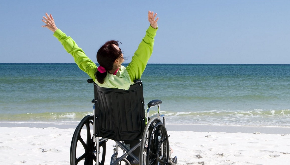Woman in a mobility wheelchair on the beach looking at the sea with her arms in the air