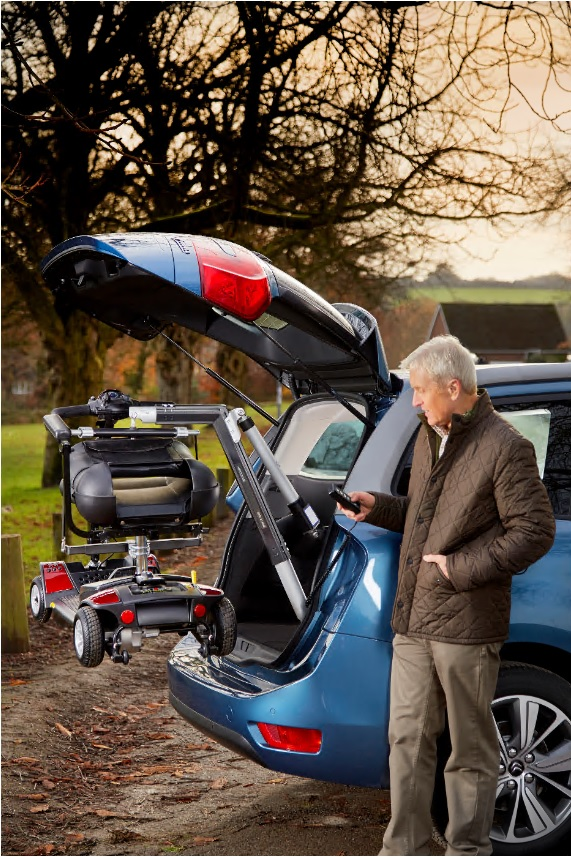 Man lowering a mobility scooter out of the back of a car with a hoist