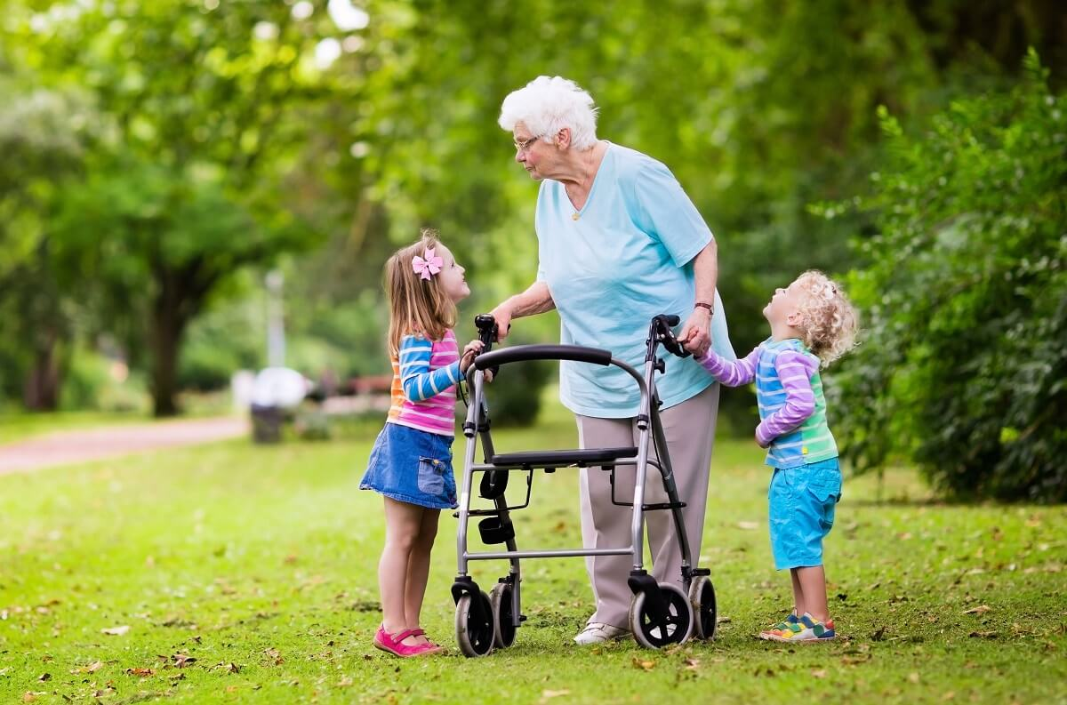 Senior lady with her grandchildren walking with a rollator