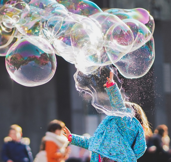 Young child in bright blue coat holds out their arm to pop large colourful bubbles