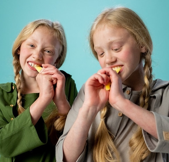 Two twin girls each bite into a chew toy