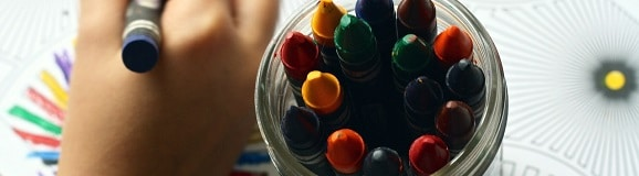 picture looking down on a jar of wax crayons showing the tips and child's hand colouring a picture