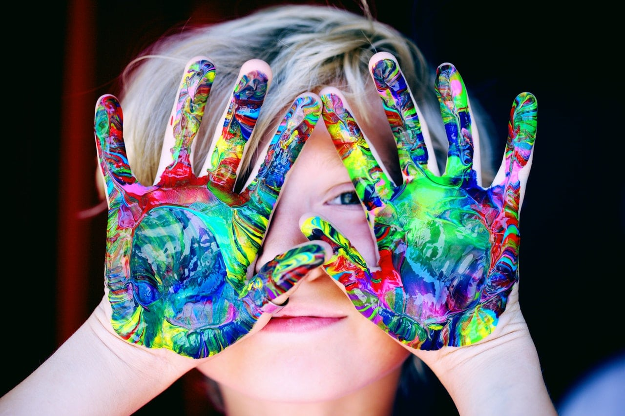 Young child holds up their hands to show that they are covered in fun colourful paint