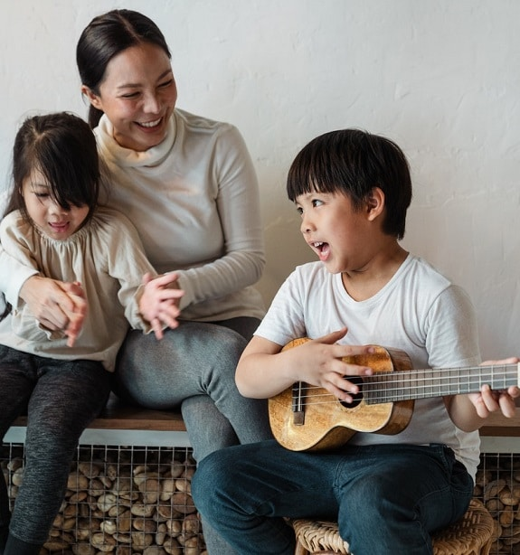 Young child strums a toy guitar while his smiling mother and sister clap in time to the music