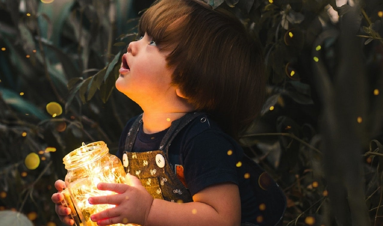 Small child looks up in wonder as they hold a jar of golden lights