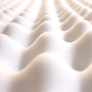 close up view of the rounded contours of a white mattress topper
