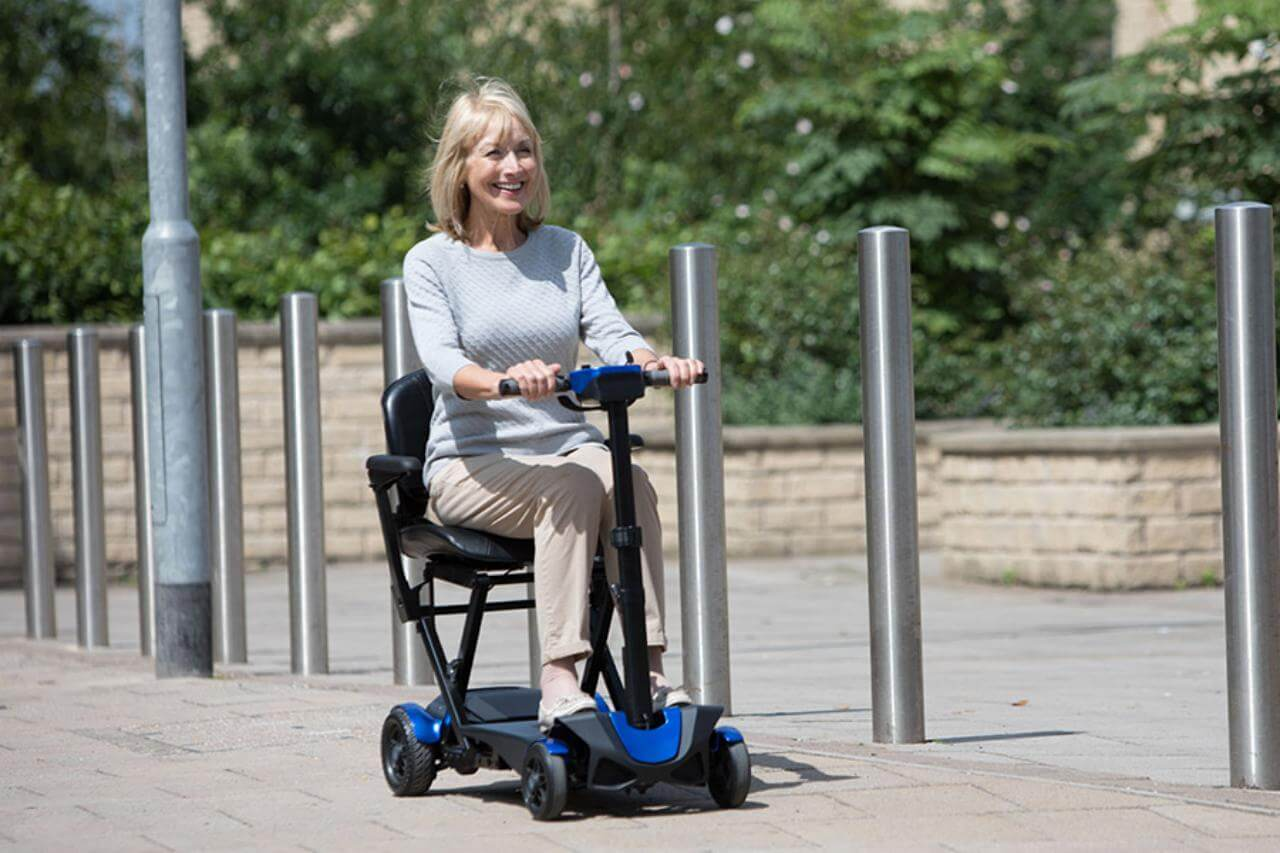 Folding mobility scooters - a lady rides along the pavement on her folding mobility scooter